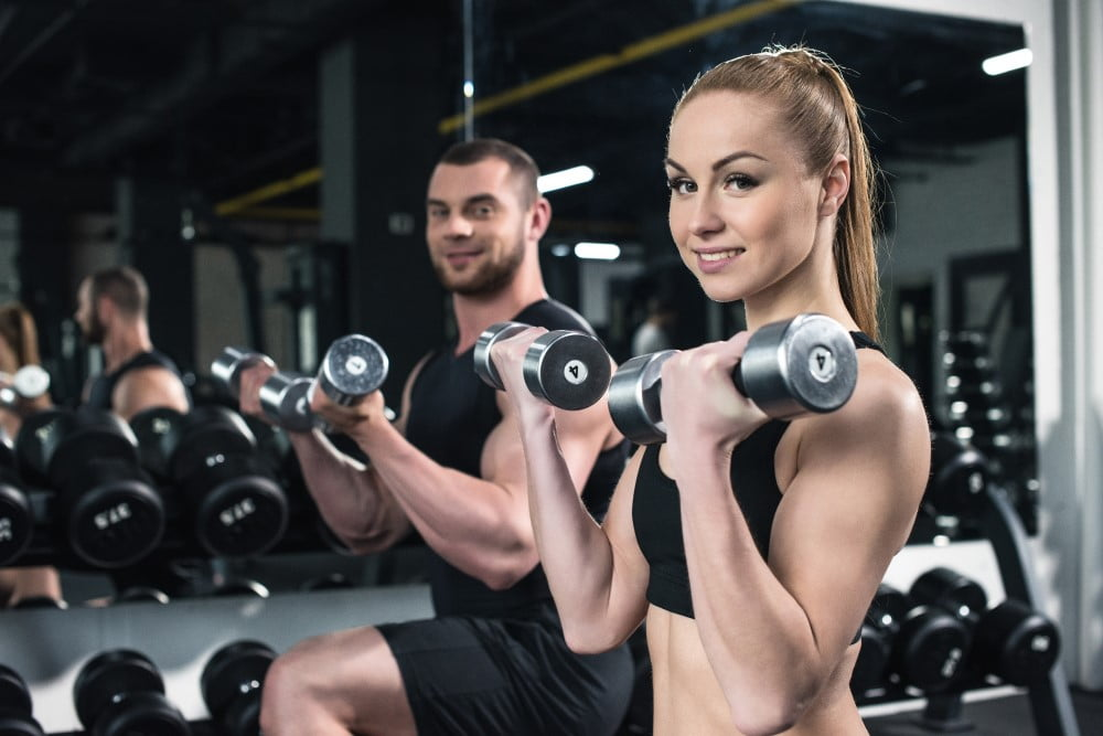 Ungt par der træner med håndvægte
